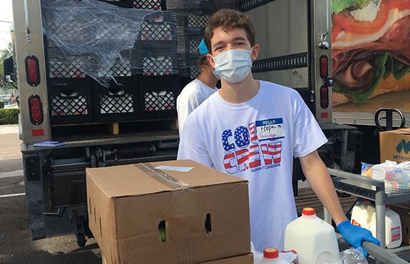 teenage volunteer loading a truck with milk