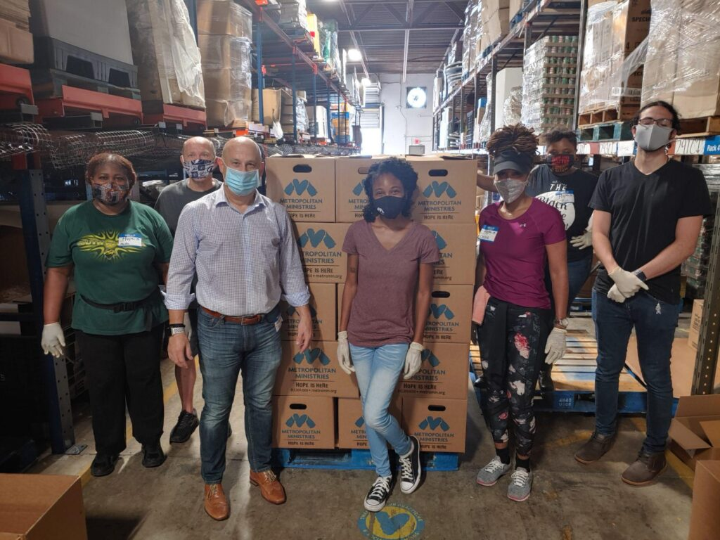 volunteers with boxes of supplies in warehouse